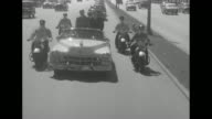 Convertible carrying Dwight Eisenhower moves slowly through crowd at airport / motorcade along highway escorted by motorcycle police / motorcade...