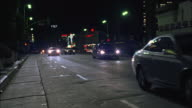 TS Convertible speedily weaving into another lane and passing other cars in light city street traffic after dark