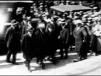 Convicted Italians Nicola Sacco Bartolomeo Vanzetti being escorted from police wagon to building steps officials stopping for photographer to take...
