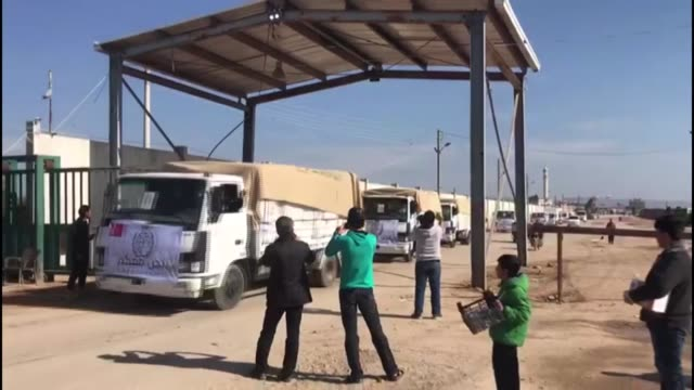 A convoy of 25 vehicles loaded with humanitarian aid by Turkish agency IHH Humanitarian Relief Foundation arrives in Syria's AlBab town after its...