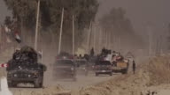 A convoy of Iraqi Army trucks and an emergency vehicle moving along a road in Mosul