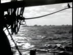 Convoy of war ships at sea Sailors in wheelhouse steering ship Sailors in rain gear on bow of ship WS Convoy on rolling ocean Sailor on deck w/...