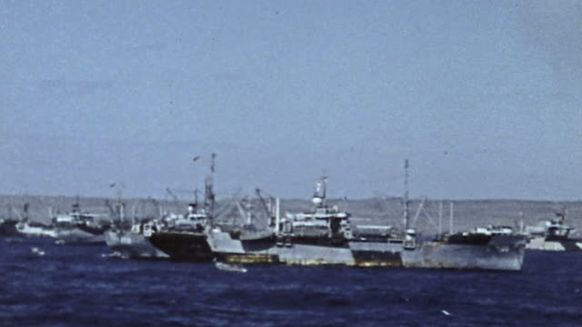 PAN Convoy of warships including an aircraft carrier sailing near the shore during World War II
