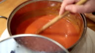 Cook Adding Spices Into Red Sauce