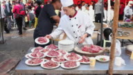 MS Cook hacked off beef in outdoor kitchen of a Wedding/xian,shaanxi,China