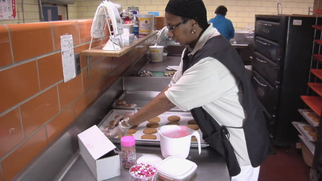 MS Cook in school kitchen applying icing to freshly baked cookies / Belleville, Michigan, USA