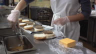 MS Cook in school kitchen preparing hamburgers with cheese slices / Belleville, Michigan, USA