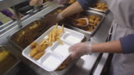 MS Cook in school kitchen serving students an assortment of French fries, onion rings and chicken pieces during lunchtime / Belleville, Michigan, USA