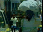 Cook meets Albright LIB DOMINICA Ext Tropical beach Boat sailing into harbour Man along carrying sack of produce on his head Flat back truck towards...