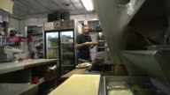MS Cook puting onions on chilli dogs at classic American diner / Ann Arbor, Michigan, United States