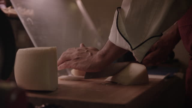 A cook slices cheese into pieces