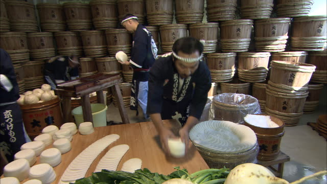 A cook spreads out slices of pickled turnip.