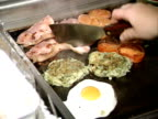 A cooked breakfast including bacon eggs and sausages is fried on a restaurant hotplate London 2000