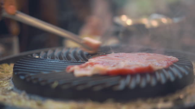 Cooking barbecue and grilled over charcoal on stove . Close up beef grilled in Japan restaurant. Raw beef slice for barbecue or Japanese style food