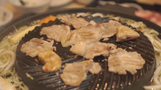 Kochen Grillen und gegrillt über Holzkohle auf Herd. Rindfleisch gegrillt in Japan Restaurant hautnah. Rohes Rindfleisch schneiden zum Grillen oder Essen im japanischen Stil