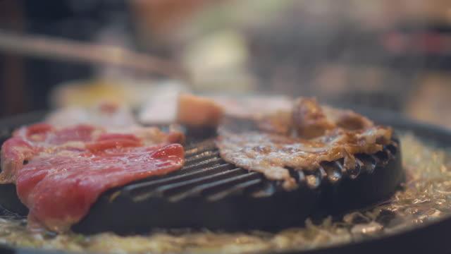 Vom Grill Grill kochen am Herd. Rindfleisch gegrillt in Japan Restaurant hautnah. Rohes Rindfleisch schneiden zum Grillen oder Essen im japanischen Stil