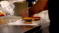Cooking fat to be used to fuel a London power station ENGLAND London INT Burgers being wrapped up by worker on counter in burger restaurant Close...