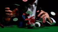 Cool gambler sitting behind chips raining down