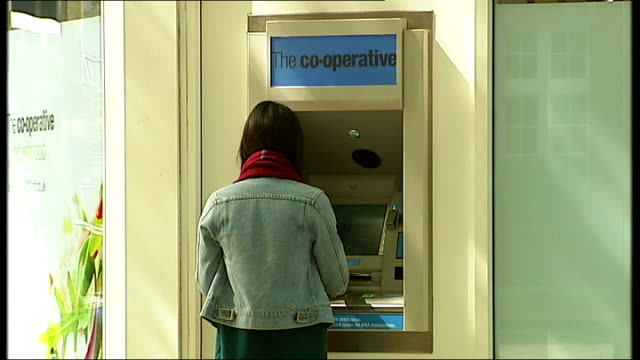 Cooperative Group delegates vote in favour of reforms at special meeting in Manchester T07051422 / TX Back view woman using ATM machine at The Coop...