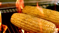 Corn being cooked on flaming barbecue