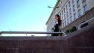 Corporate gekleidet weibliche diskutieren über das Telefon und die Treppe hinunter.
