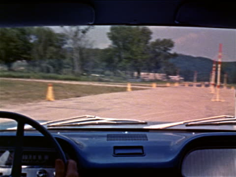 1960 Corvair point of view driving around poles on test track / man's hands on steering wheels visible