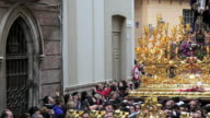 Costaleros bearing a Trono a religious float during Semana Santa, a procession through the streets of Malaga, Spain, Europe