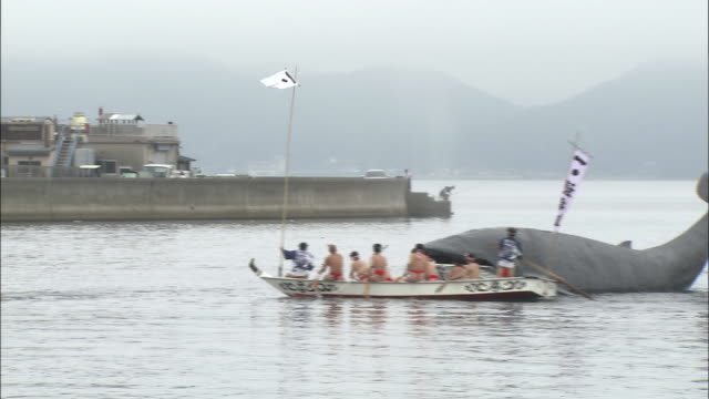 Costumed men on boats surround an artificial whale during a festival.
