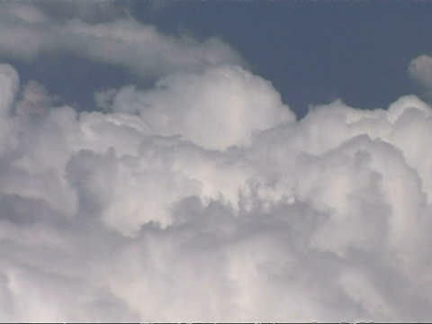 Cotton wool clouds against blue sky from aircraft window, CU, Europe