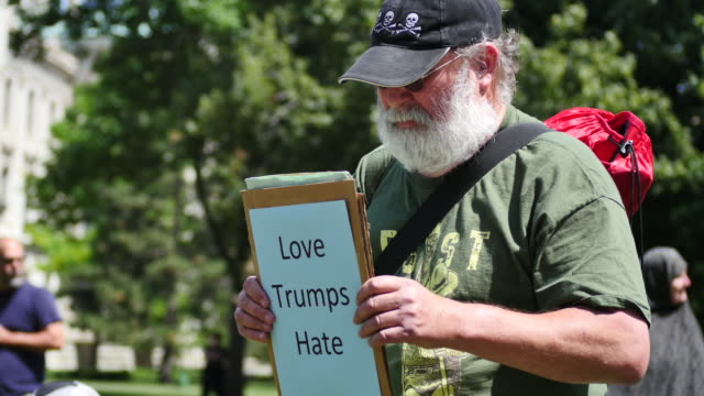 A counter protester holds a sign reading 'Love Trumps Hate' on one side and 'I stand with my Muslim brothers and sisters' on the other side during...