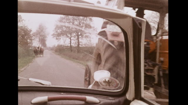 VS Country road trees man driving tractor horsedrawn carriage cows grazing brick buildings female hitchhikers INTERCUT VS Man in convertible driver's...