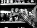 1950 MONTAGE country store clerk takes two cans off a shelf and puts them on the counter / Southville, Kentucky, United States