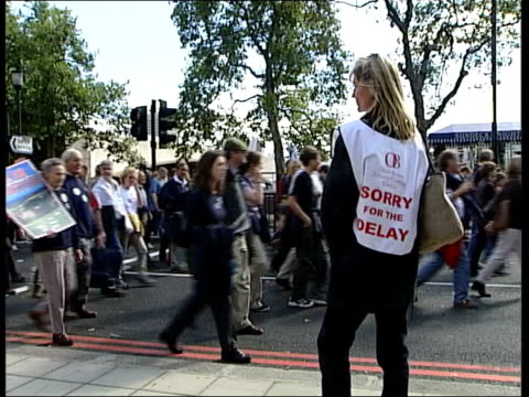 London Marchers towards and past SPEEDED UP marchers towards and past MS Man out of portable toilet as BV another enters Angle GV Line of portable...