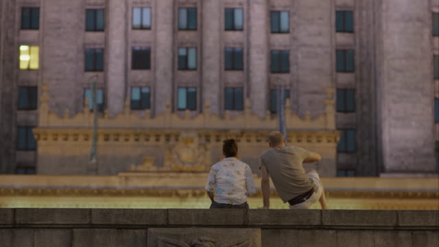 Couple against the background of a concrete wall.