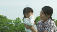 PAN Couple and daughter playing in park