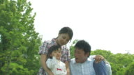 Couple and daughter playing in park