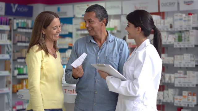 Couple at a drugstore talking with a pharmacist about their prescription