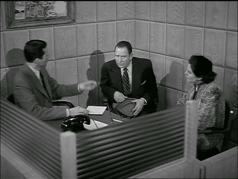 B/W 1954 couple + banker signing contract at desk / man hesitates + smiles before signing