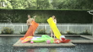 Couple blowing up inflatable beds by swimming pool
