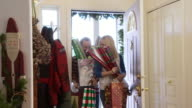 Couple bringing presents and wrapping paper in through the front door / Bellevue, Idaho, United States