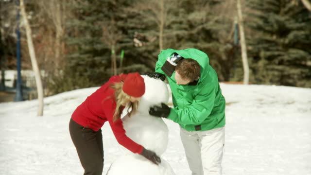 Couple builds a snowman