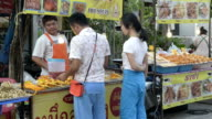 A couple buy grilled squid in a food stall