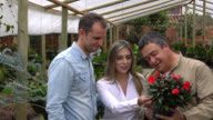 Couple buying a flower plant and salesman helping them