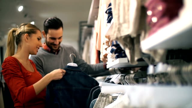 Couple buying clothes at retail store.