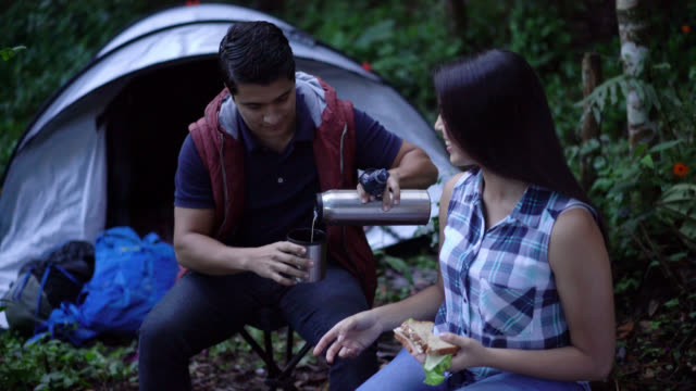 Couple camping outdoors having fun talking and smiling