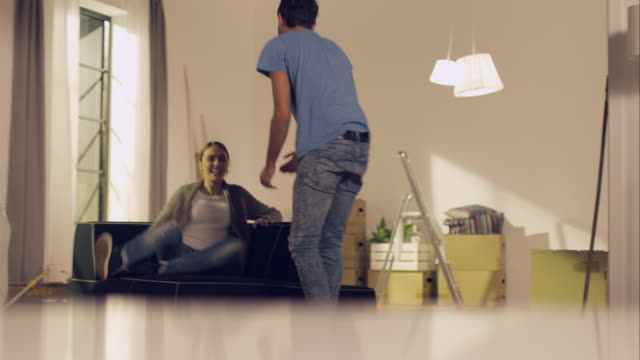 Couple carrying couch into new apartment and sit down