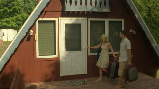 MS, Couple carrying suitcases entering holiday cabin, Fish Creek, Wisconsin, USA