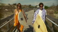 MS Couple carrying surfboards, walking down boardwalk towards beach / Long Beach, New York State, USA