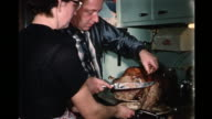 1959 HOME MOVIE Couple carving turkey in kitchen / Toronto, Canada