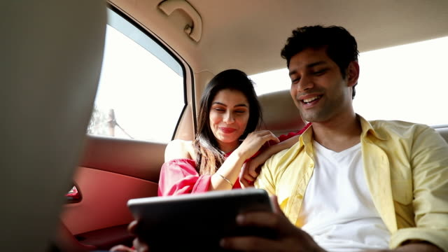Couple chatting on digital tablet in the car, Delhi, India